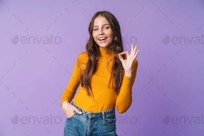 Image of young beautiful woman smiling and gesturing okay sign