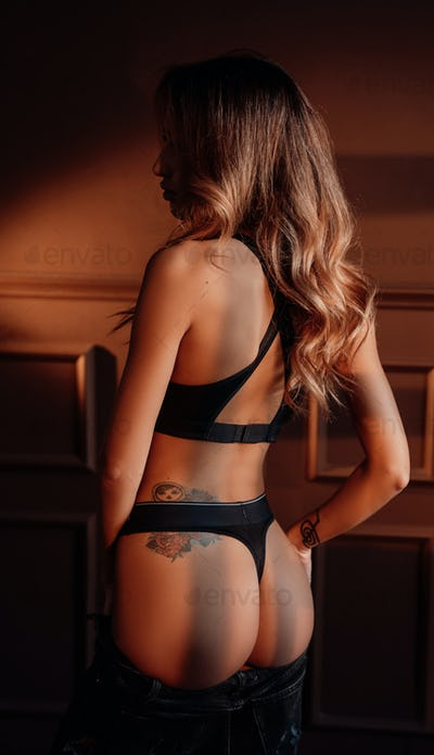 Gorgeous woman showing her body wearing sportive black lingerie in a dark apartment