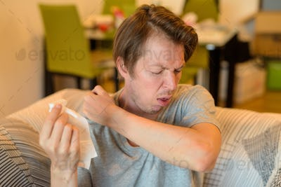 Face of sick young man coughing into elbow while in quarantine at home