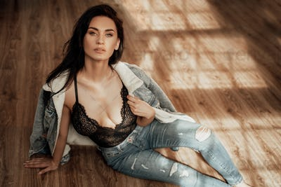 Luscious young woman sitting on the floor wearing black top and jeans costume