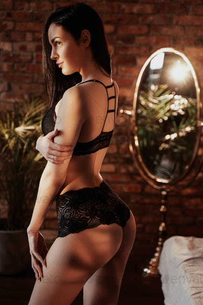 Sexy young caucasian woman posing in a luxury flat wearing sexy lace lingerie