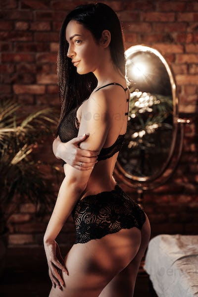 Sensual young caucasian woman posing in a luxury flat wearing sexy lace lingerie