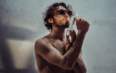 Handsome young man being shirtless and illuminated with sun in a studio while smoking a pipe