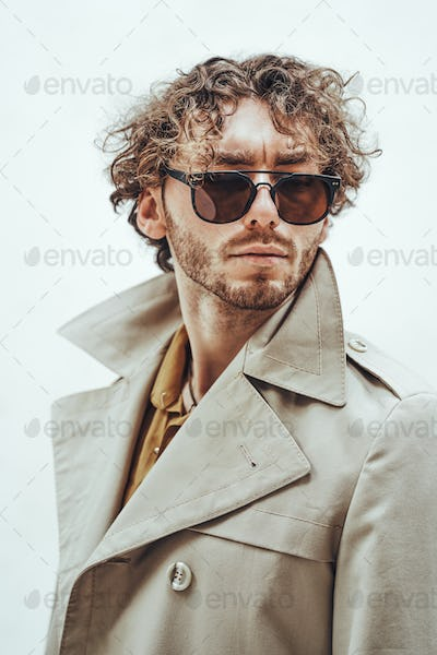Portrait of a handsome casual guy with curly hair posing in the bright studio