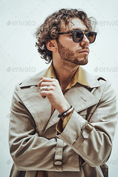 Handsome and good-looking man with curly hair posing for the photoshoot on the bright background