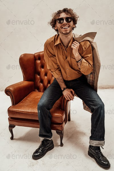 Handsome casual guy with curly hair posing in the bright studio while sitting on leather chair