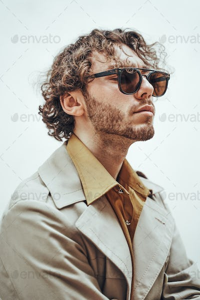 Handsome young caucasian man with curly hair  posing in a bright studio, wearing elegant clothes