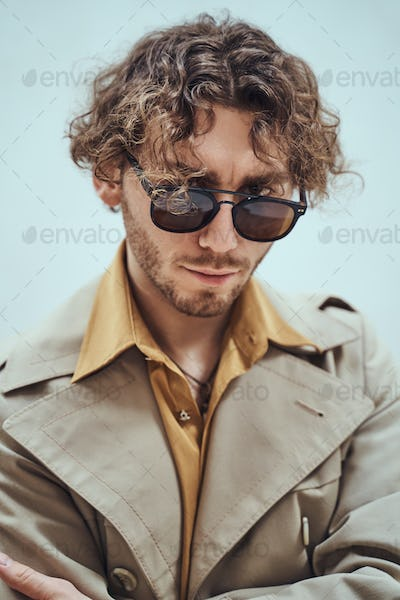Thoughtful and curly man wearing sunglasses posing in the bright studio looking rich