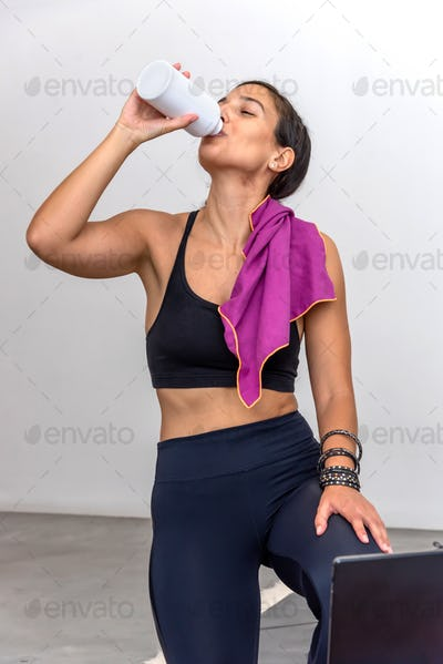 Woman drinking water after practicing yoga at home