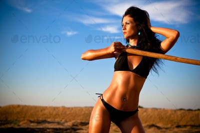 Young woman in black bikini standing outdoors with wooden stick in hand