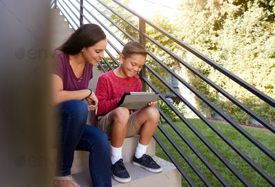 Mother Sitting On Steps Outdoors At Home With Son Using Digital Tablet