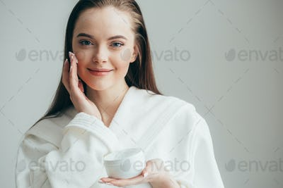 Beautiful groomed woman's hands holding a cream jar on the fluffy blanket. Moisturizing