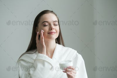 Beautiful young girl in a bathrobe, smiling and smears a cheek with white cream.