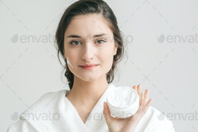 Face cream female portrait, woman in bathroom with cream on face age concept