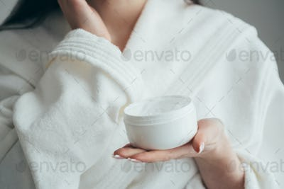 Beautiful groomed woman's hands holding a cream jar on the fluffy blanket. Moisturizing cream