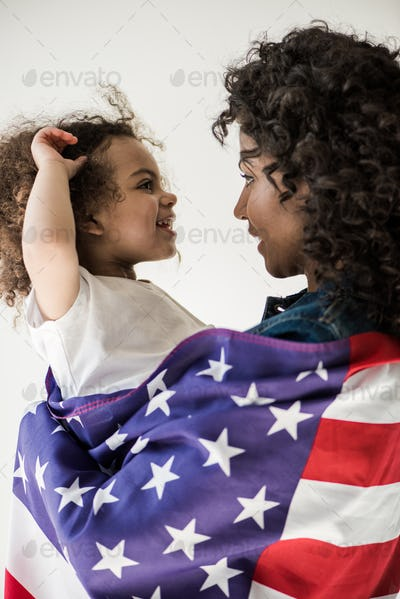 Loving African American Mother Covered With American Flag Embrace Daughter