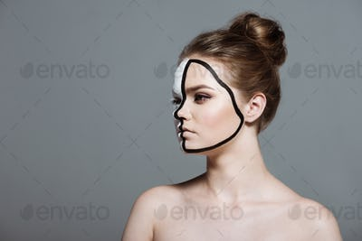 Young Girl With Creative White and Black Bodyart on Face, Isolated on Grey