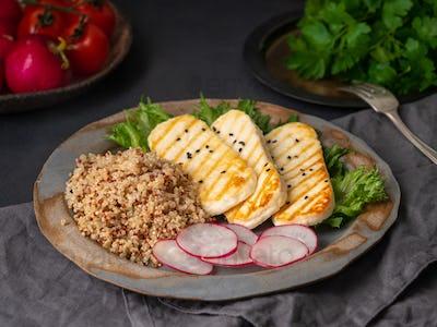Halloumi, grilled cheese with quinoa, salad, radish. Balanced diet on  dark background, side view