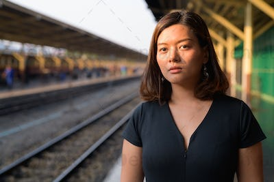 Young beautiful Asian tourist woman thinking at the railway station