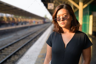 Young beautiful Asian tourist woman waiting at the railway station