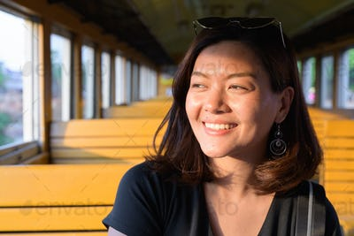 Face of happy young beautiful Asian tourist woman smiling inside the train