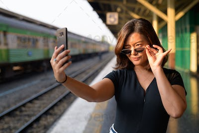 Young beautiful Asian tourist woman taking selfie at the railway station