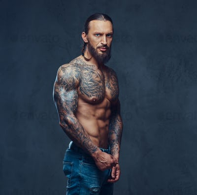 Portrait of a muscular bearded tattooed male with a stylish haircut, isolated on a dark background