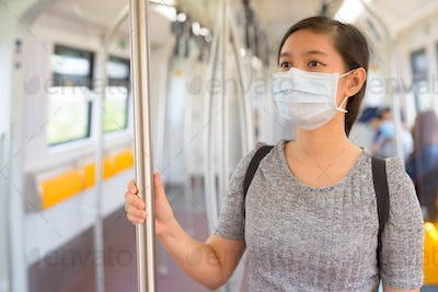 Young Asian woman wearing mask and standing with distance inside the train for protection from