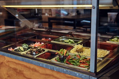 Close-up image of metal containers with different vegetables for fast food take away in the cafe.