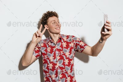 Image of smiling man taking selfie and gesturing peace sign