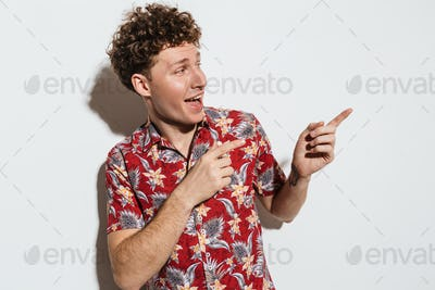 Image of caucasian delighted man smiling and pointing fingers aside