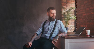 Handsome tattooed hipster in an office with loft interior.
