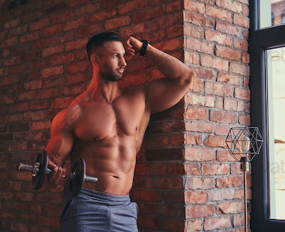 Tall stylish shirtless bodybuilder dressed in sports shorts in a room with a loft interior.