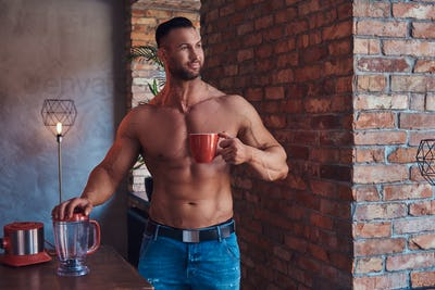 Tall stylish shirtless bodybuilder dressed in jeans, standing in a room with a loft interior.