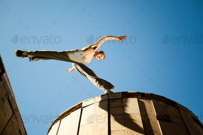 Young man jumping and practicing parkour between buildings roofs outside on clear summer day with