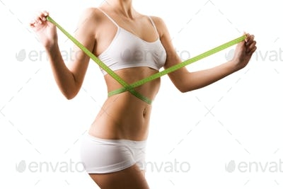 Body of young woman in white shorts and top measuring waist with tape measure in hands over white