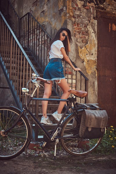 Slim fashionable girl posing with bicycle near an old building.
