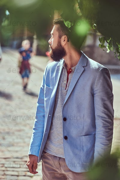 A fashionable bearded male wearing stylish clothes, stands on an antique street in Europe.