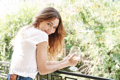 Image of caucasian young woman smiling and drinking wine outdoors