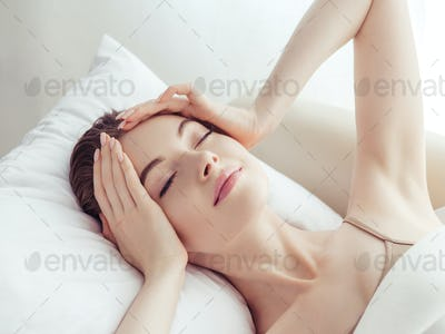 Stressed woman home headache pain female portrait. Girl close face head hands at sofa  alon sad.