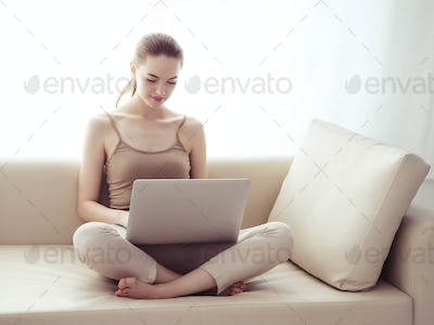 Beautiful Young Woman with Computer at home on sofa.