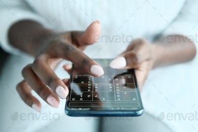 Black Woman Playing Sudoku On Phone