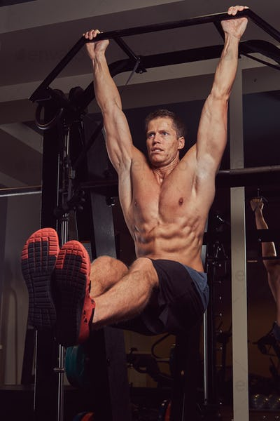 Muscular shirtless man doing push-ups on the horizontal bar in the gym.