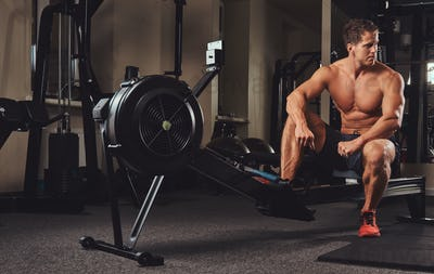 Muscular shirtless athlete resting after a hard workout while sits on the rowing machine in the gym.