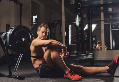 Muscular shirtless athlete sits on a floor resting after a hard workout in the gym.
