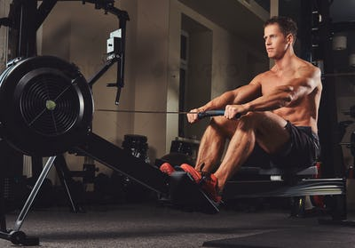 Handsome muscular fitness male doing exercise on the rowing machine.