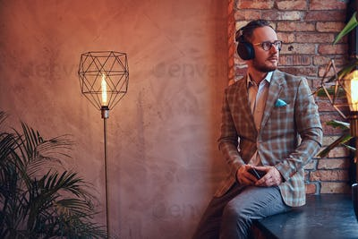 Stylish man in a flannel suit and glasses listening music in a room with loft interior.