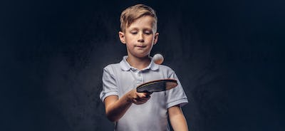 Cute redhead boy dressed in a white t-shirt playing ping-pong in a studio