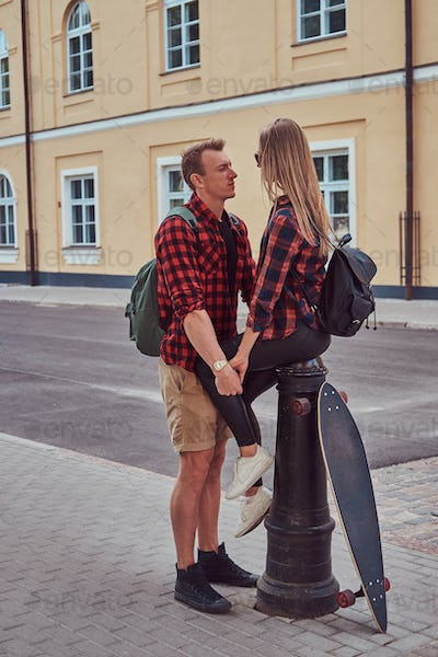 Handsome skater holding hands his girlfriend who sitting on a fire hydrant in an old Europe street.