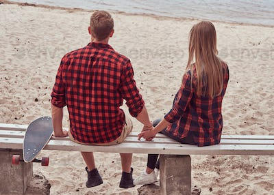 Back view of a cute hipster couple, sits on a bench in the middle of the beach and watch a sea.